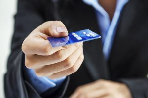 man holding a blue credit card