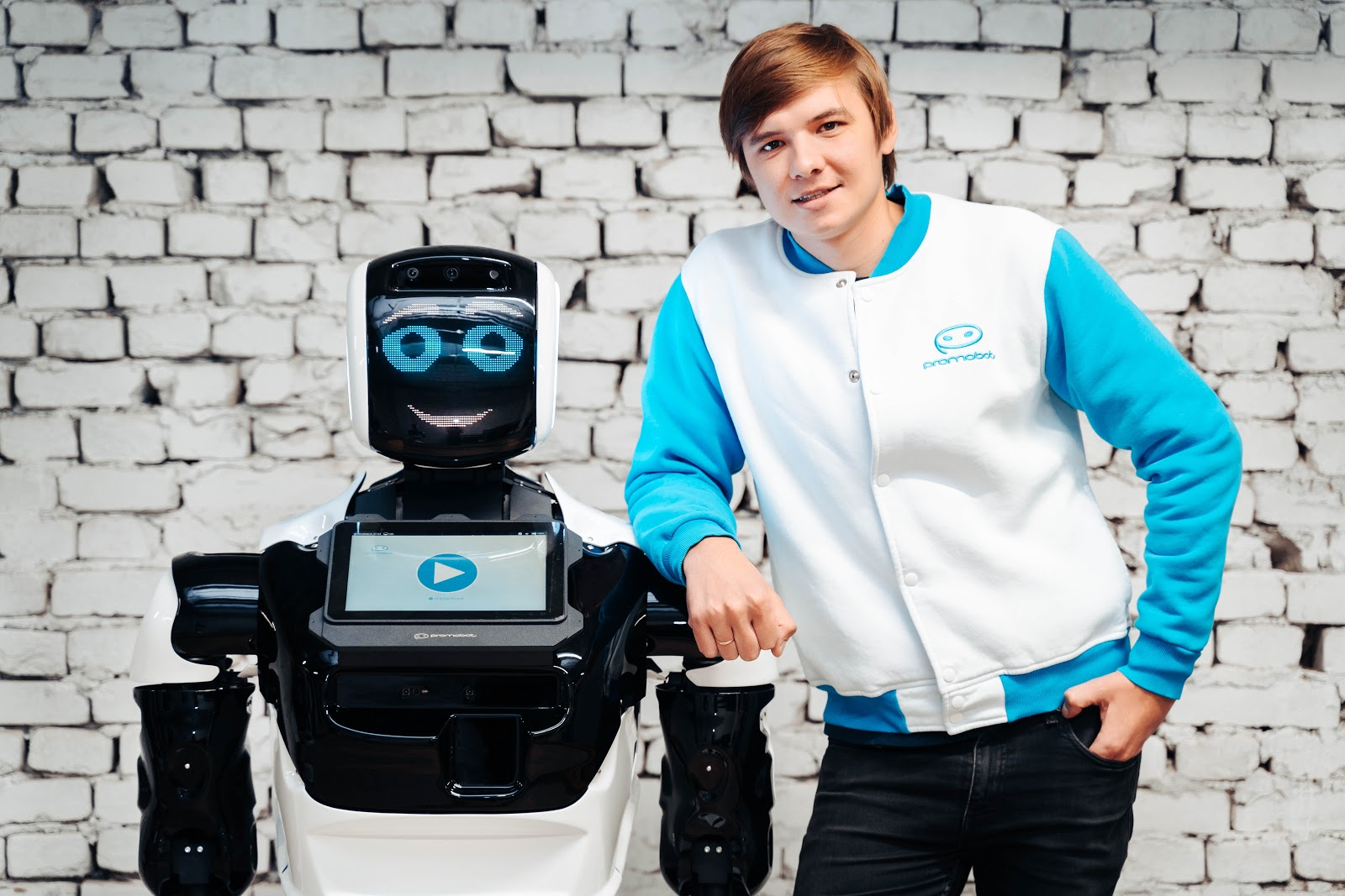 young man standing next to a robot