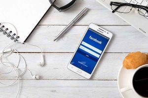 phone with facebook app open, pen and headset