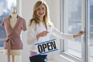 woman putting up open sign