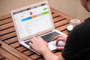 man in black shirt working laptop