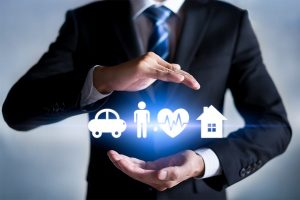 Businessman with protective gesture and insurance icons