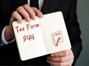 Man Holding A Notebook wit Tax Form 944 Written