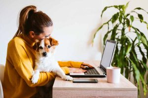 woman cuddling her pet while working from home