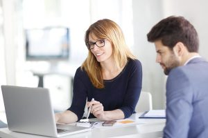 businesswoman sitting at office in front of computer and consulting with young professional man