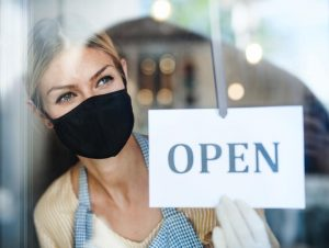 """Woman holding an """"Open"""" signage"""