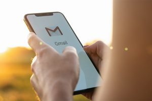 woman holding a iPhone with Google Gmail app logo on the display