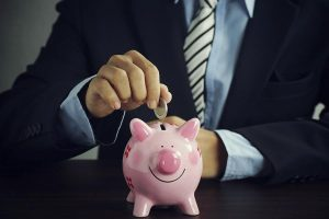 man holding coin and piggy bank