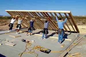 A group of construction workers raising a wood frame for a house