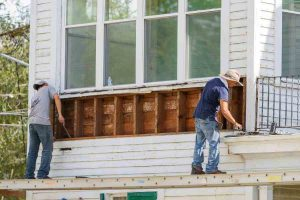 Workers removing siding from old house