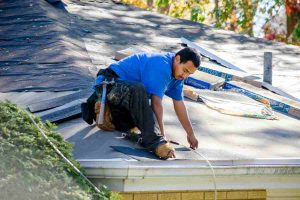 A Worker rehabs a home by replacing a roof with fresh shingles using an electric nail gun
