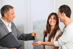 businessman handing over key to the couple