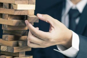 businessman playing wood block tower