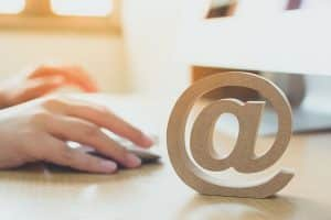 Hand using computer sending message with wooden email address symbol