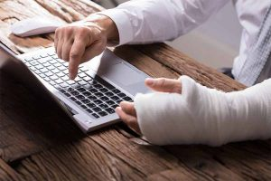 man typing on keyboard with injured left hand
