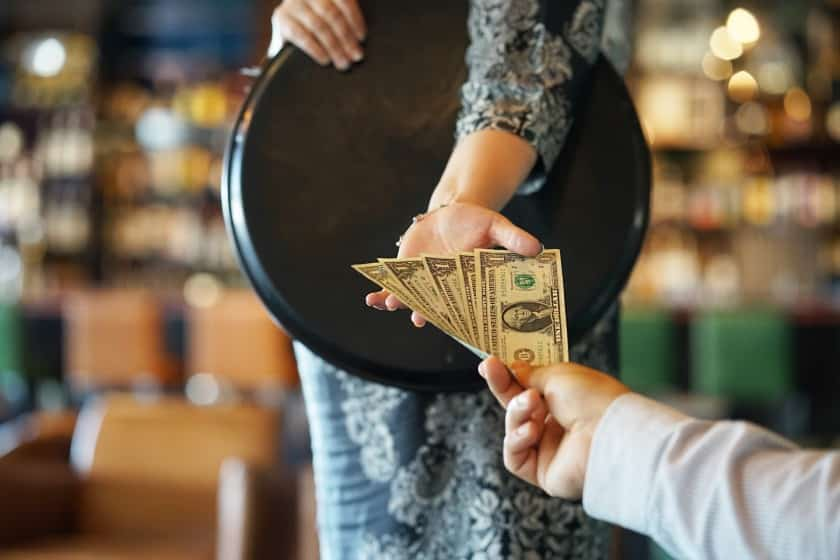 Image of a man giving or paying bill on waitress