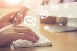 guy typing on keyword while email icons flying around