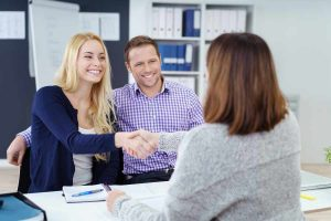 couple shaking hands with female employee