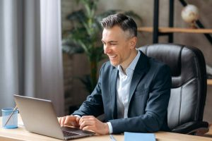 businessman happily working on his laptop