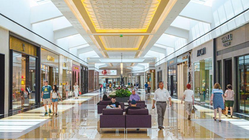 Shoppers Walk Through a Shopping Center Full of Stores