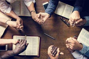 people holding hands and bible