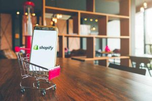 Mobile Phone with Shopify Logo on Screen Placed on a Small Shopping Cart