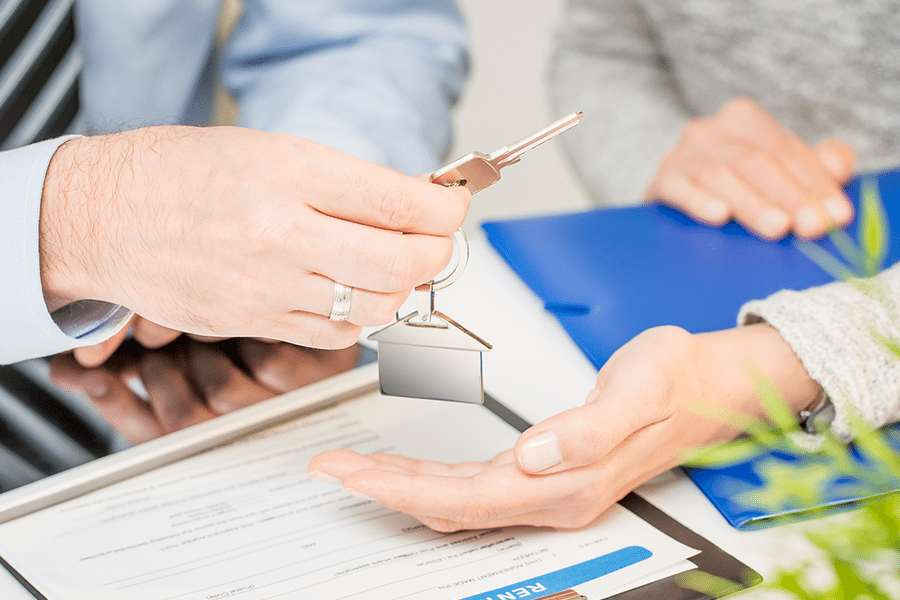 Real estate agent handling the house key to the new home owner