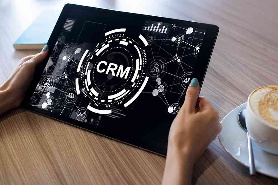 hand holding a tablet with CRM on screen