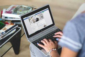 woman browsing facebook on laptop
