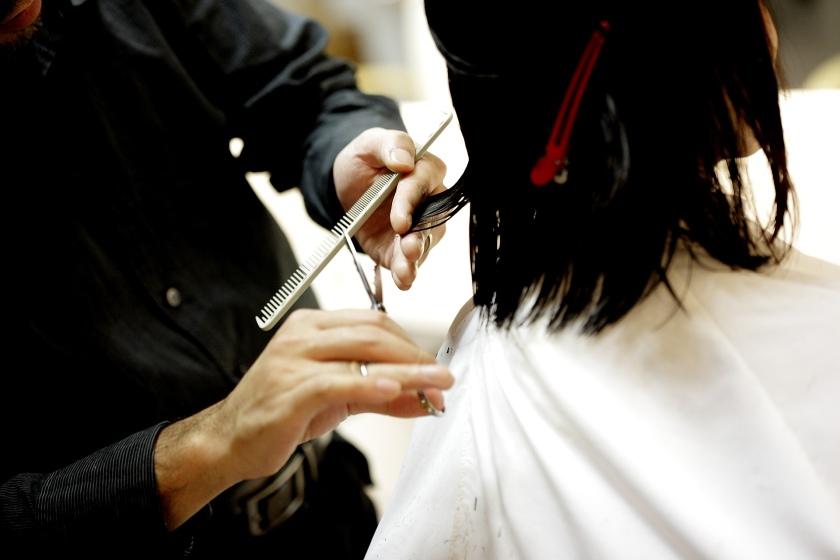 Barber cutting woman hair