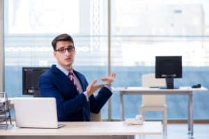 Office guy pointing to the desk of an absentee colleague