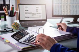 Businessperson's Hand Calculating Invoice