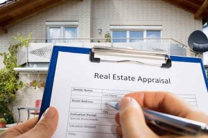 Close-up Of Person Hand Filling Real Estate Appraisal Document