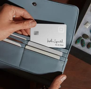 Screenshot of girl holding card from pocket