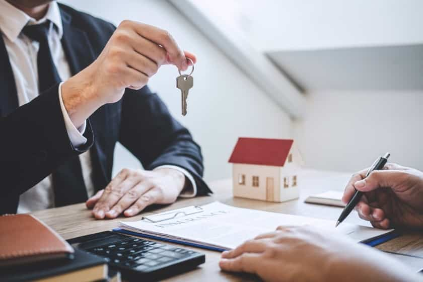 Real Estate agent giving house keys to client
