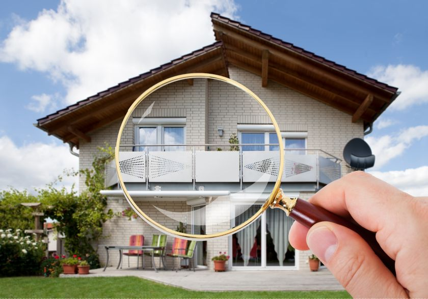 Person Hand With Magnifying Glass Over Luxury House