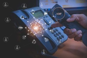 Hand of man using ip phone with icon of voip services