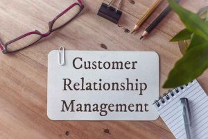 In the notebook is the text of Customer Relationship Management, next to a pencil and glasses.
