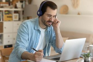 man sitting in headphones by laptop listening taking notes