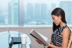 businesswoman reading documents studying paperwork at desk
