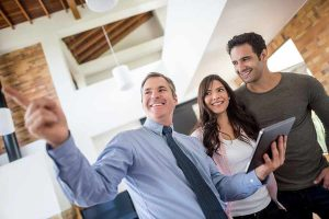 Male realtor showing new house to couple