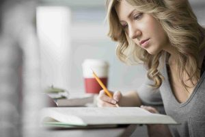 young adult woman studying and taking notes