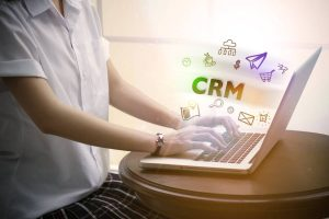 woman typing CRM over notebook computer with icon